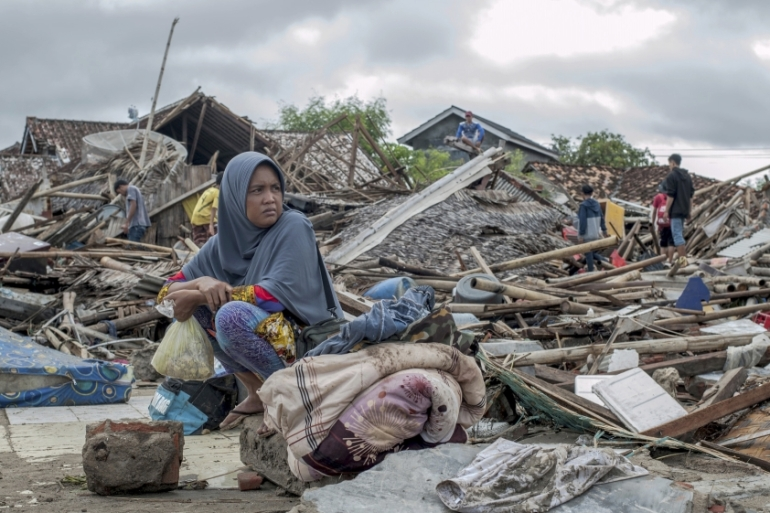 A tsunami survivor sits on debris as she salvages items from her house in Sumur, Indonesia [Fauzy Chaniago/AP Photo]