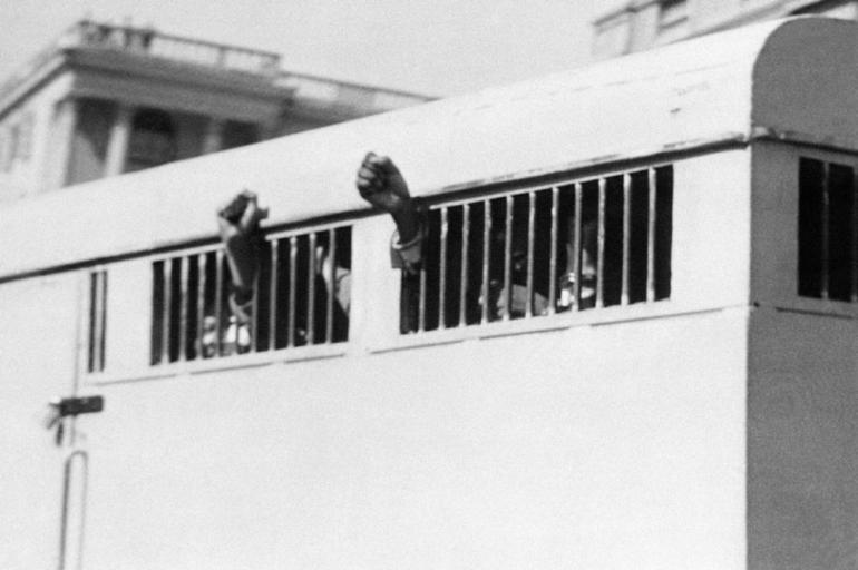 Convicted in 1964, Mandela and seven others were sentenced to life in prison. As they were taken away from the Palace of Justice, they raised their fists in defiance through the barred windows of the prison van.