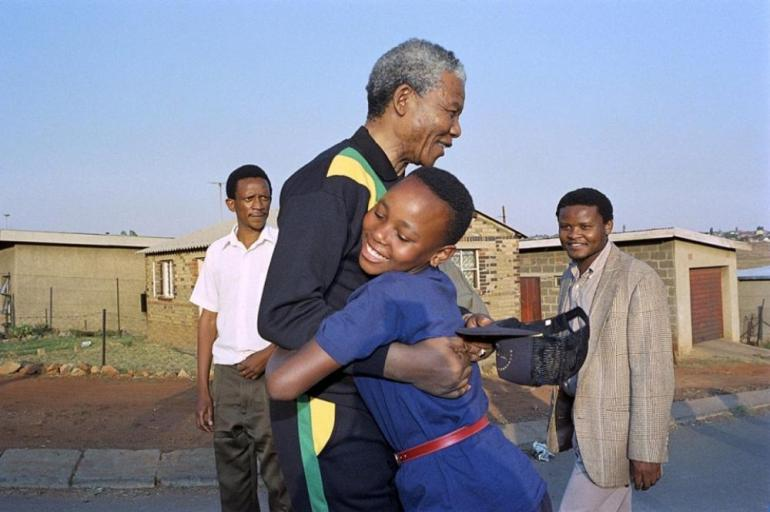 In the months after his release, Mandela was greeted with joy almost everywhere he went. Here he is hugged by a girl in the the black township Soweto in October 1990.