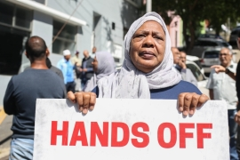 Bo Kaap resident Fowzia Achmat holds up a sign at a protest [Erica Jenkin/Al Jazeera]