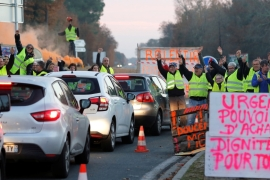 Protesters wearing yellow vests occupy a roundabout in Cissac-Medoc, France on December 5, 2018. The slogan reads 'Urgent, purchase power, dignity for all' [Regis Duvignau/Reuters]