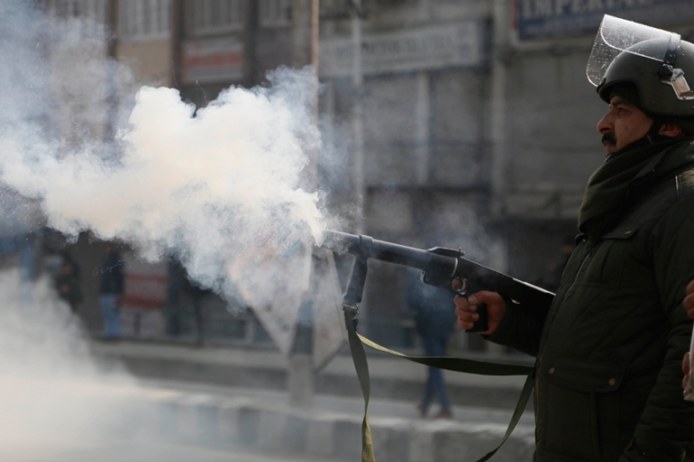 An Indian police officer fires tear smoke shell on Kashmiri protesters on December 17 [Mukhtar Khan/AP]