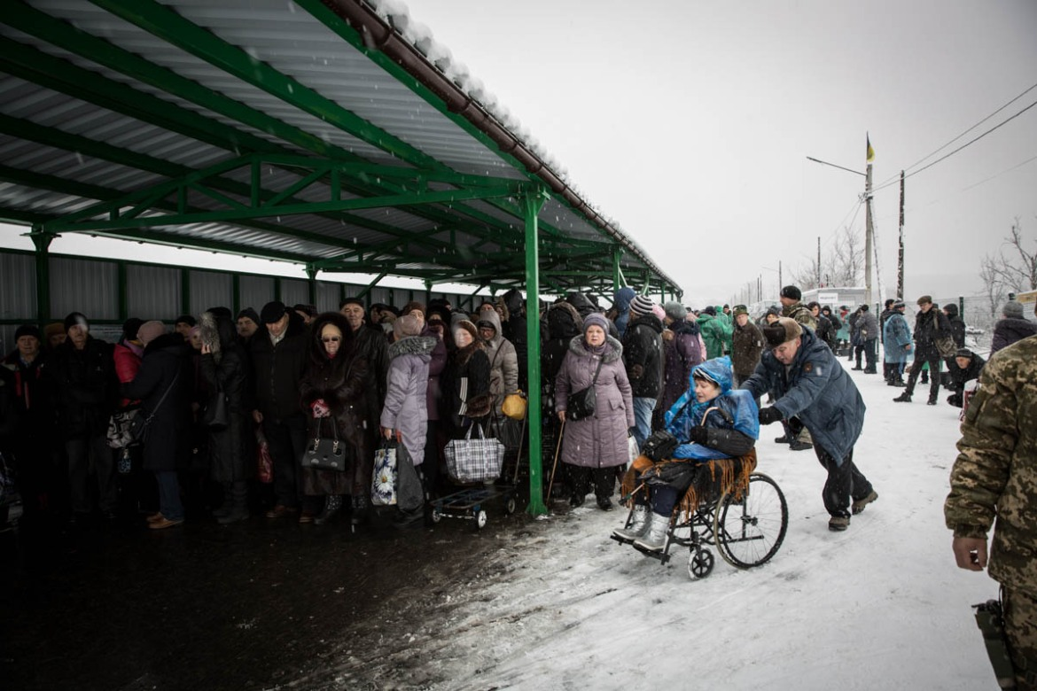 Every day, thousands of people, many of them elderly, have to cross the checkpoint dividing government-controlled and non-government-controlled areas at Stanytsia Luhanska. The bridge is destroyed, making it impossible for cars to pass and forcing people to walk for several kilometres through no man's land and wait for three-four hours to pass each way. [Ingebjorg Karstad/Norwegian Refugee Council]