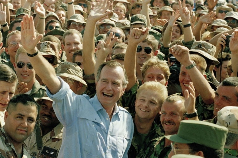 In this November 22, 1990 file photo, President George HW Bush poses with US soldiers during a stop at an airbase in Dhahran, Saudi Arabia [File:Scott Applewhite/AP]