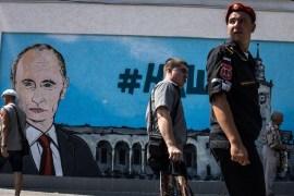 People walk by fresh graffiti depicting Vladimir Putin in Simferopol on August 17, 2015, in Simferopol, Crimea. [Alexander Aksakov/Getty Images]
