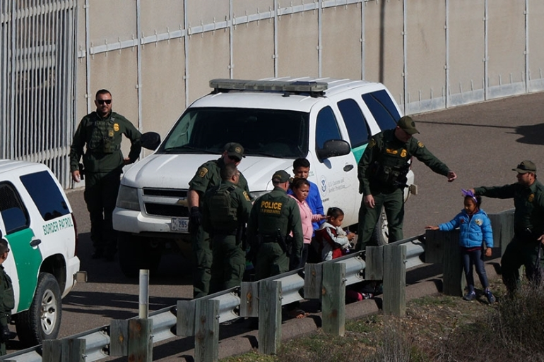 A woman and children are ushered into cars by US Border Patrol agents after crossing the border wall into San Diego, California [File: Rebecca Blackwell/AP Photo]