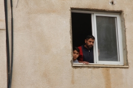 Murad and his son Laith, 9, peek from the window of their home, a day before demolition is set to take place [Ibrahim Husseini/Al Jazeera]
