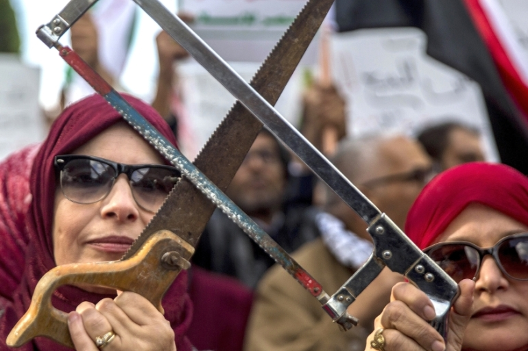 Tunisians demonstrate with saws on Tuesday November 27 in Tunis against the visit of Saudi Crown Prince Mohammed bin Salman to the country [Hassene Dridi/AP]