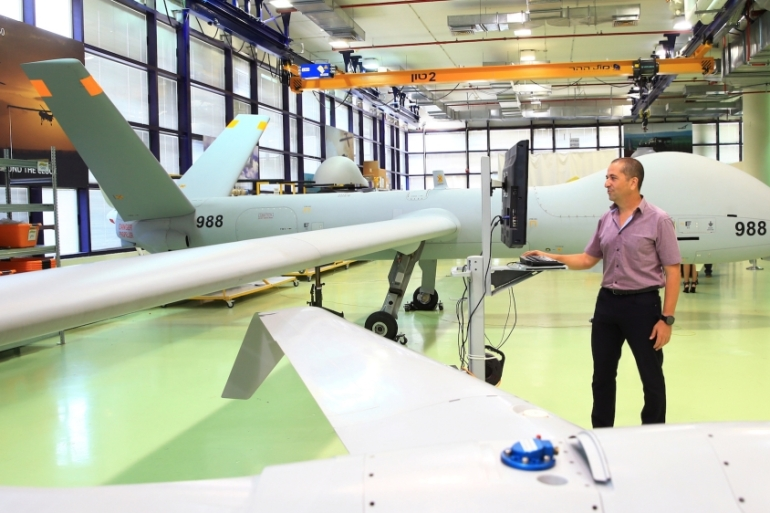 An employee stands next to an Elbit Systems Hermes 900 UAV at the company's drone factory in Rehovot, Israel on June 28, 2018 [File: Orel Cohen/Reuters]