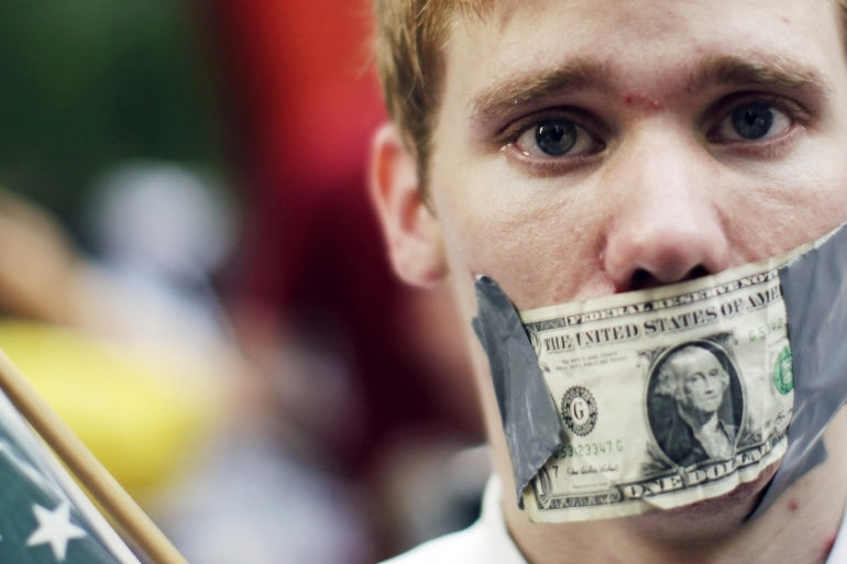 A demonstrator from the Occupy Wall Street campaign seen with a dollar taped over his mouth as he stands near the financial district of New York September 30, 2011 [File: Lucas Jackson/Reuters]