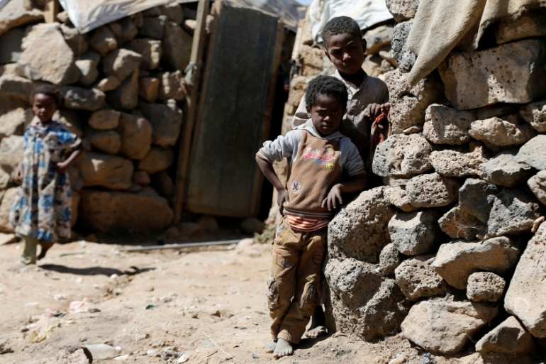 Children stand near their hut at a makeshift camp for internally displaced people near Sanaa last month [Khaled Abdullah/Reuters]