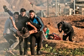 In this file photo, Palestinians carry away a protester, injured by Israeli forces along the Gaza Strip's perimeter fence [File: Mahmud Hams/AFP]