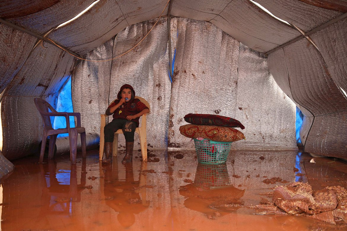 The few possessions the refugees had were ruined by filthy, muddy water. [Aaref Watad/AFP]