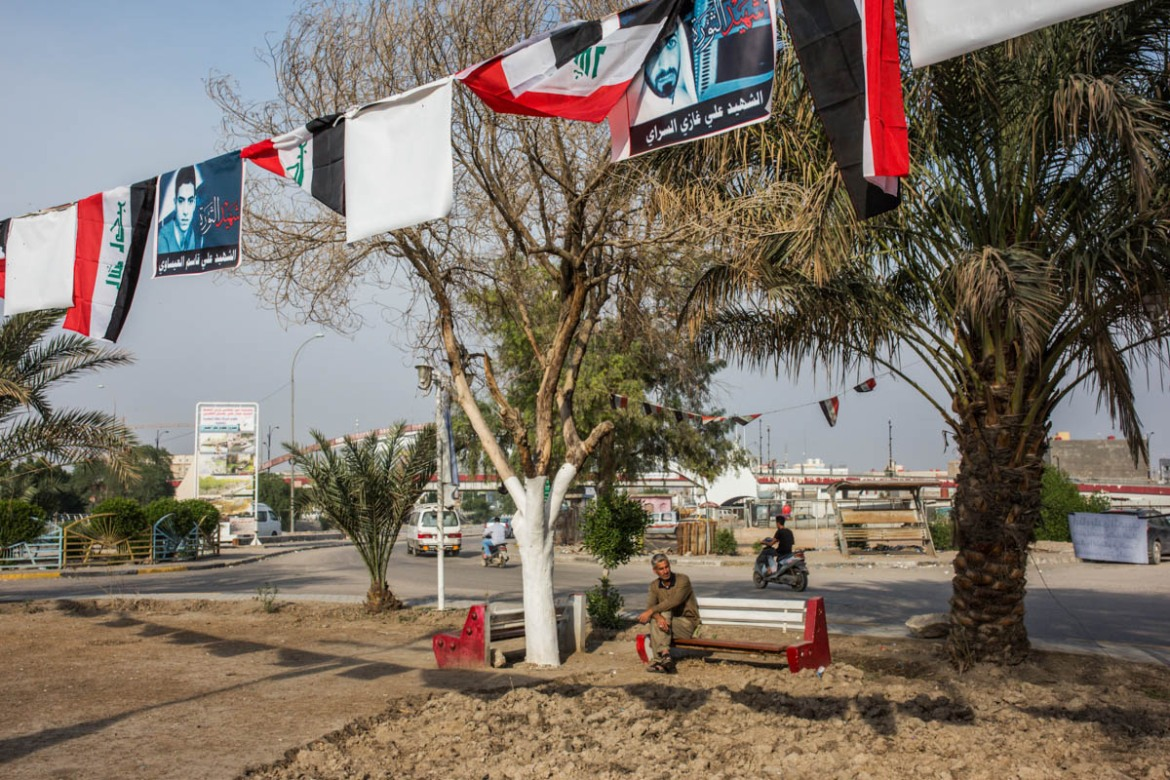 A man sitting on a bench in Abdel Karim Qassem Square, the site of last year's protests against water crisis, corruption and youth unemployment. Photos of the 20 people killed during Basra 2018's Revolution, as the activists refer to the protests, hung near the square. [Alessio Mamo/Al Jazeera]