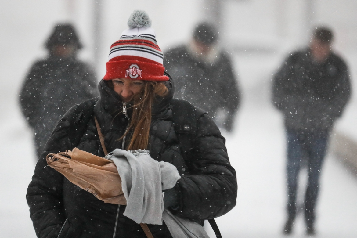 Commuters brave the wind and snow in frigid weather in Cincinnati. The extreme cold and record-breaking temperatures are crawling into a swathe of states spanning from North Dakota to Missouri and into Ohio after a powerful snowstorm pounded the region earlier this week. [John Minchillo/AP Photo]