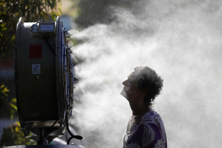 A tennis fan cools down in front of a mist sprayer during the Australian Open tennis tournament in Melbourne [EPA-EFE/MAST IRHAM]