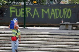 "A man walks past graffiti on the wall of a vacant lot that reads in Spanish, ""Get out Maduro"" [Fernando Llano/AP Photo]"