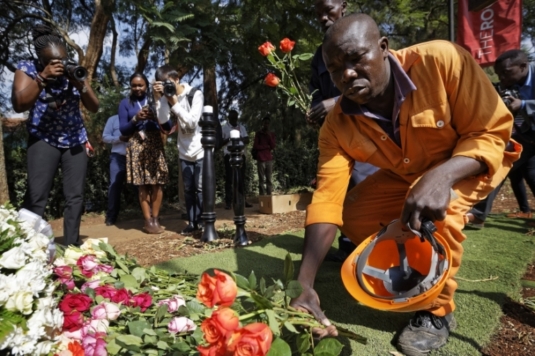 A worker lays flowers in honor of the dead outside the gate of the Dusit Hotel complex which was attacked last week, in Nairobi, Kenya Tuesday, Jan. 22, 2019 [Ben Curtis/AP Photo]