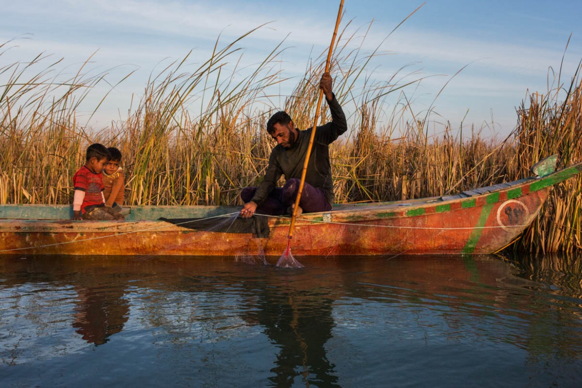 A man fishes together with his two sons at the Chebayesh marsh. [Alessio Mamo/Al Jazeera]