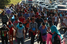 A group of migrants begin their journey towards the US border as they walk along a highway in San Salvador [Salvador Melendez/AP]