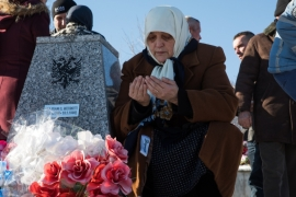 A woman prays at the gravesite of a loved one at Racak, Kosovo on the 20th anniversary of the massacre [Valerie Plesch/Al Jazeera]