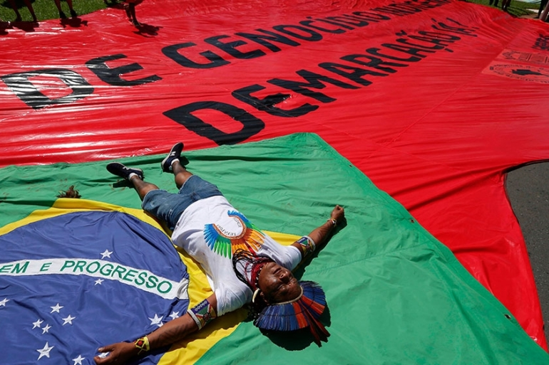 An indigenous man lies on top of a Brazilian flag representing the natives killed in the struggle for their lands, next to a large red flag reading 'Indigenous Genocide, Demarcation now!' [File: Eraldo Peres/AP Photo]