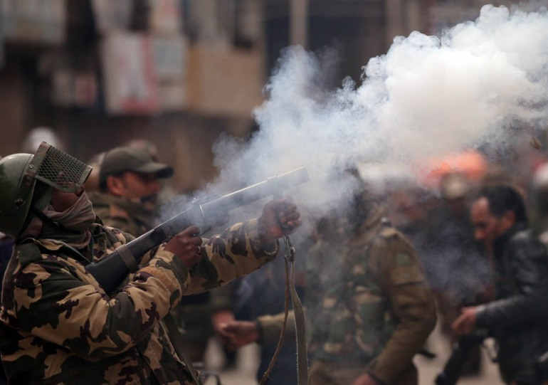 A member of the Indian Central Reserve Police Force (CRPF) fires a tear gas shell during a protest by Kashmiri demonstrators after India's National Investigation Agency (NIA) members carried out a raid at the residence of Yasin Malik, Chairman of Jammu Kashmir Liberation Front (JKLF), a separatist party, in Srinagar. [Danish Ismail/Reuters]