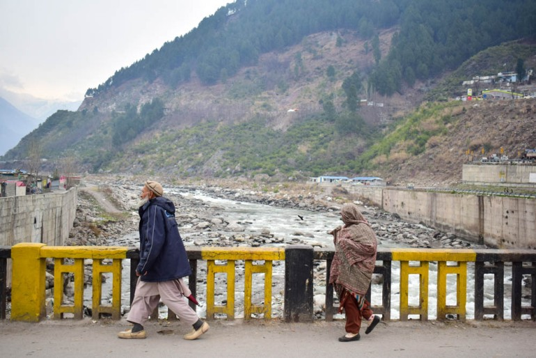 Pakistanis walk across a bridge in the mountainous area of Balakot where the Indian Air Force (IAF) launched a raid. [Jameel Ahmed/AFP]