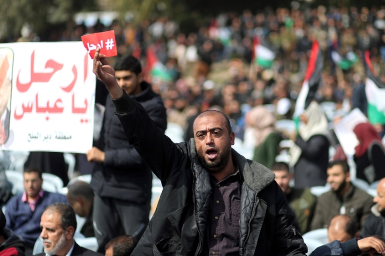 A demonstrator holds a sign reading 'leave' during a Gaza Strip protest against Mahmoud Abbas [Mohammed Salem/Reuters]