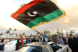 Libyans wave national flags as they gather in the capital Tripoli's Martyrs Square, to celebrate ahead of the eighth anniversary of the Libyan revolution [Mahmud Turkia/AFP]