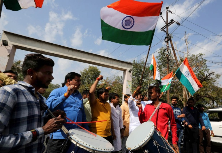 India's ruling Bharatiya Janata Party (BJP) workers hold the national flag in Bhopal city as they celebrate on the streets after the Indian Air Force carried out raids inside Pakistan. [Sanjeev Gupta/EPA]