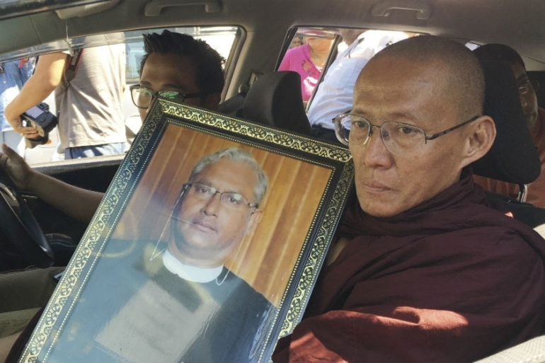 A Buddhist monk holds a portrait of Ko Ni, legal adviser and prominent member of Myanmar's Muslim minority, during his funeral in Yangon,  [File: Esther Htusan/AP Photo]