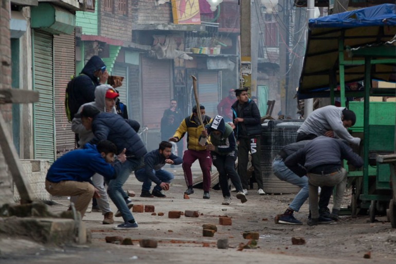 Kashmiri protesters run for cover as they clash with Indian policemen in Srinagar, the capital of Indian-administered Kashmir. [Dar Yasin/AP Photo]
