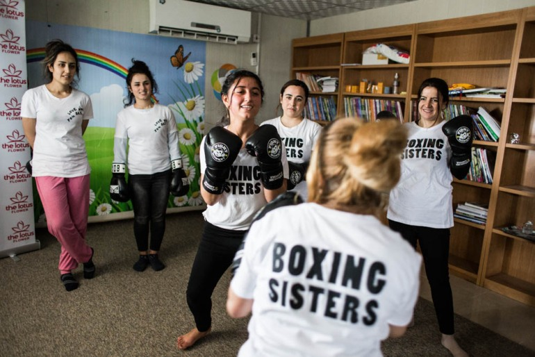Husna, 17, spars with Cathy Brown, a retired professional British boxer and certified cognitive behavioural therapist. Brown will train a few women to become trainers themselves, so they can share their skills with other women of the community. [Giacomo Sini/Al Jazeera]