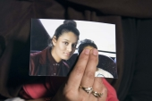 Renu Begum, eldest sister of Shamima Begum, 15, holds her sister's photo as she is interviewed by the media at New Scotland Yard [File: Getty/Laura Lean]