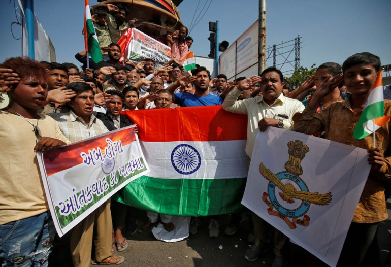 People hold national flags and an Indian Air Force flag in Ahmedabad as they salute to celebrate after India said its fighter jets conducted air raids on rebel camps in Pakistani territory. [Amit Dave/Reuters]