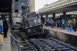 Firefighters and onlookers gather at the scene of a fiery train crash at the Egyptian capital's main railway station on February 27, 2019 [Anadolu]