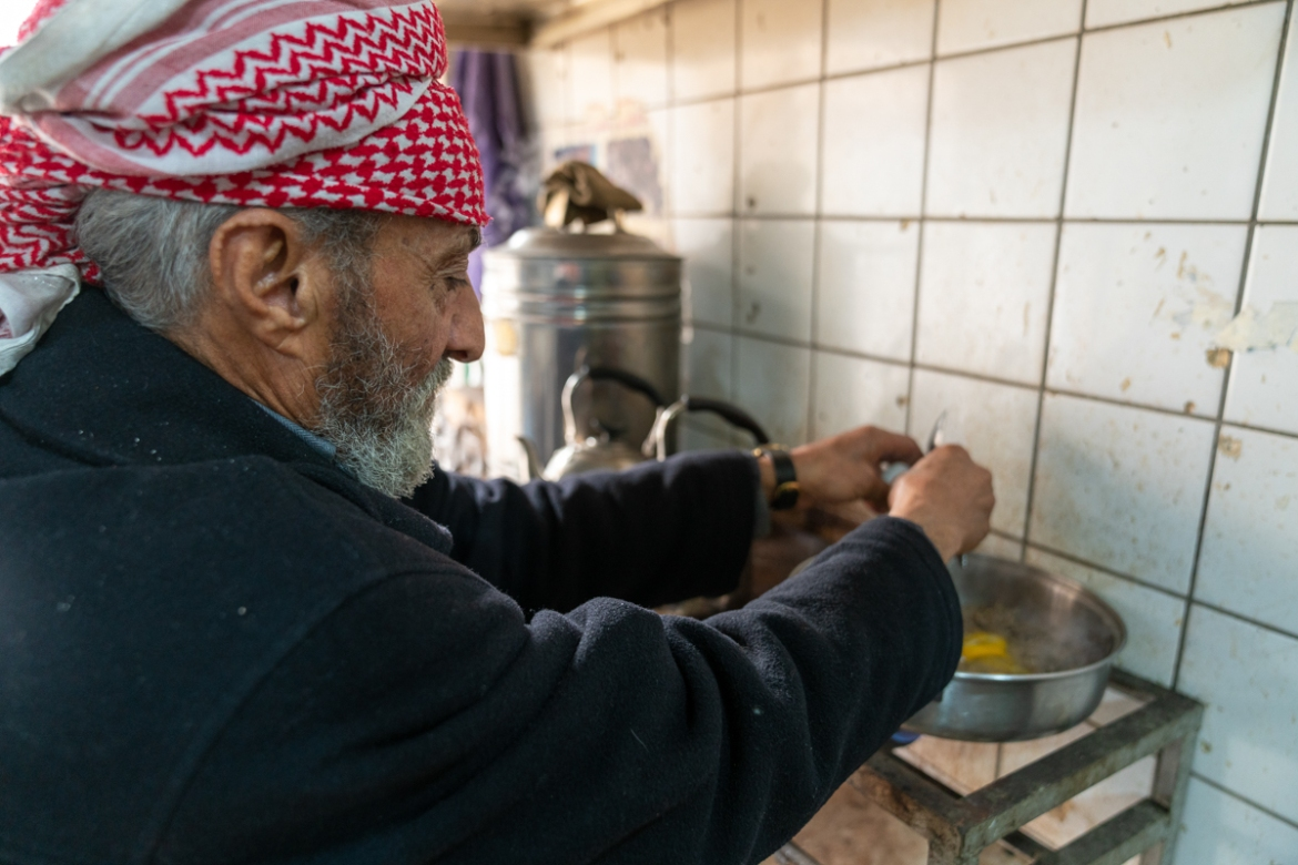 Qassim Yahya, 75, prepares breakfast inside a tea shop in the Old City. He says that he has seen hundreds of people beheaded or thrown off buildings by the ISIL fighters. [Emre Rende/Al Jazeera]