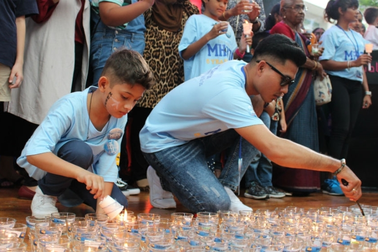 Family members light candles for each of the 239 people who were on board MH370 [Kate Mayberry/Al Jazeera]