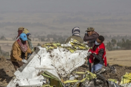 Rescuers work at the scene of an Ethiopian Airlines flight crash near Bishoftu, or Debre Zeit, south of Addis Ababa, Ethiopia, Monday, March 11, 2019. A spokesman says Ethiopian Airlines has grounded all its Boeing 737 Max 8 aircraft as a safety precaution, following the crash of one of its planes in which 157 people were killed. (AP Photo/Mulugeta Ayene) [The Associated Press]