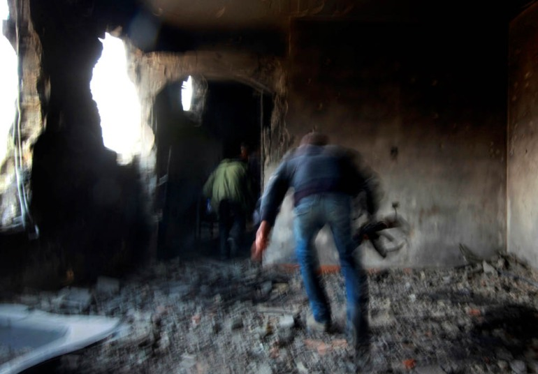 Rebel fighters run for cover inside a building on the frontline in Tripoli street in central Misrata - April 21, 2011. [Yannis Behrakis/Reuters]