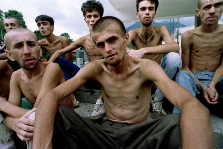 Emaciated Muslim refugees, recently released from a Croat prison in Dretelj, wait for lunch in a grammar school in Jablanica, central Bosnia - September 10, 1993. [Yannis Behrakis/Reuters]