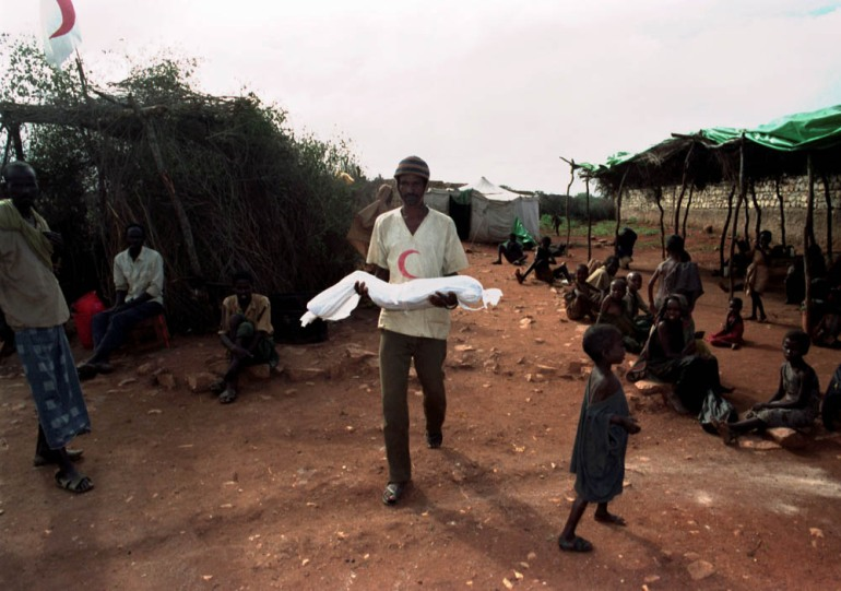 A Somali aid worker carries a dead child for burial in a Baidoa refugee camp - Somalia, December 15, 1992. [Yannis Behrakis/Reuters]