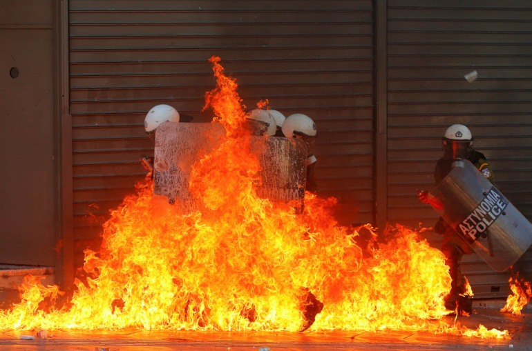 A group of riot policemen is engulfed in flames after protesters threw petrol bombs in Athens' Syntagma square during a 24-hour labour strike - September 26, 2012. [Yannis Behrakis/Reuters]