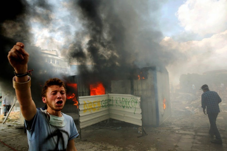 An anti-government protester shouts for help to extinguish a burning container on Taksim square in Istanbul, Turkey - June 4, 2013. [Yannis Behrakis/Reuters]