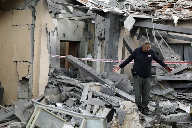 A police sapper inspects a damaged house that was hit by a rocket north of Tel Aviv [Ammar Awad/Reuters]