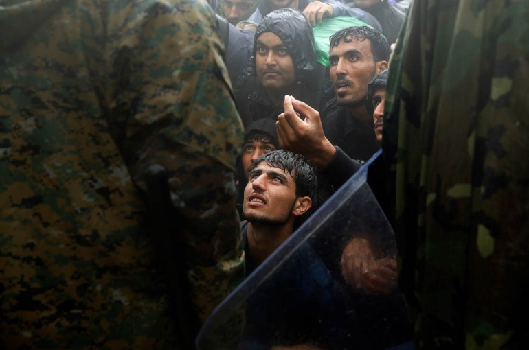 Migrants and refugees beg policemen to allow passage to cross the border from Greece into North Macedonia during a rainstorm near Idomeni - September 10, 2015. [Yannis Behrakis/Reuters]