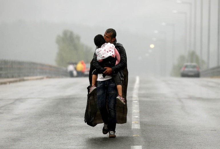 A Syrian refugee kisses his daughter as he walks through a rainstorm towards Greece's northern border near the village of Idomeni - September 10, 2015. [Yannis Behrakis/Reuters]