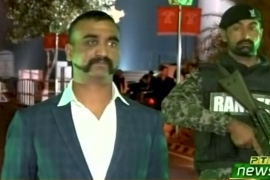 Wing Commander Abhinandan Varthaman stands under armed escort near Pakistan-India border in Wagah [Reuters/PTV via Reuters TV]