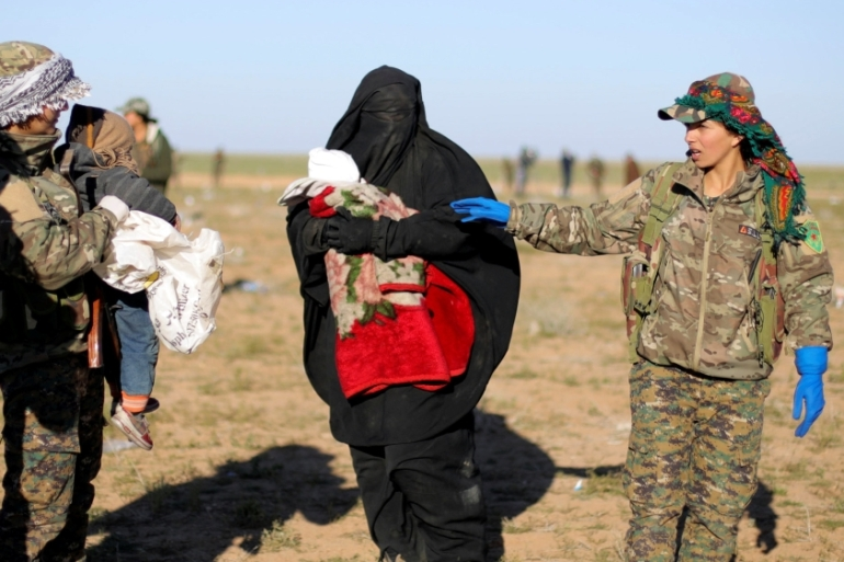 A woman holds a baby as she stands next to female fighters from Syrian Democratic Forces near Baghouz [Rodi Said/Reuters]